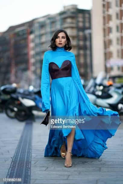 Karina Nigay wears a blue ruffled flowing dress, a black bustier, a black bag, golden shoes, outside Versace, during Milan Fashion Week Fall/Winter...