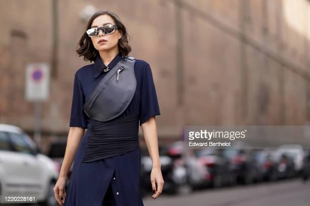 Karina Nigay wears mirror sunglasses, a fanny pack bag, a blue dress, outside Sportmax, during Milan Fashion Week Fall/Winter 2020-2021 on February...