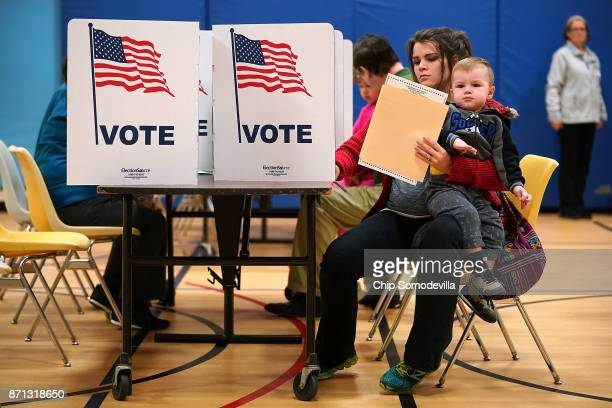 Karina Smith holds her 2-year-old son Kyler as she fills out her ballot at the polling place at Washington Mill Elementary School November 7, 2017 in...