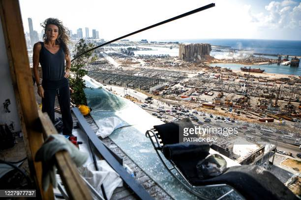 Karina Sukkar, a Lebanese architect and designer, stands the balcony of her damaged apartment overlooking the ravaged port of Lebanon's capital...