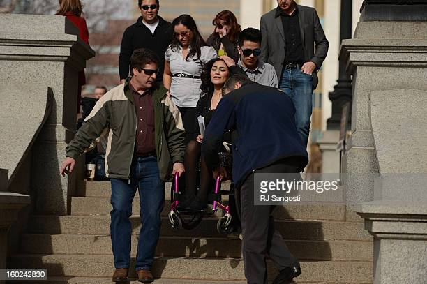Karina Vargas center who was paralyzed from a shooting outside Aurora Central High School is helped down the steps after attending a rally against...