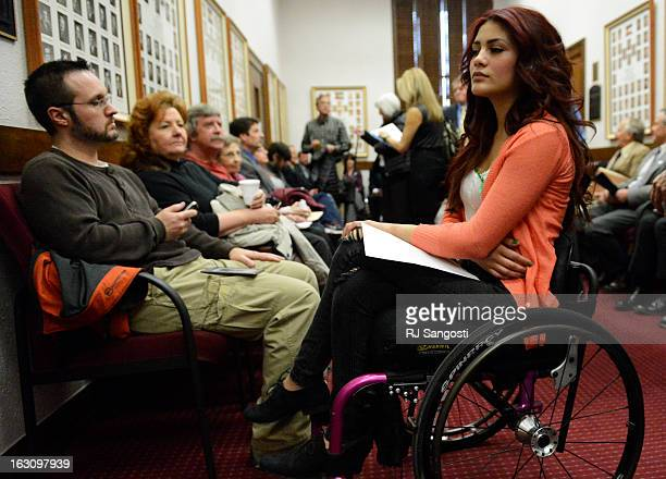Karina Vargas right who was paralyzed from a shooting outside Aurora Central High School waits to testify before Colorado lawmakers at the Colorado...