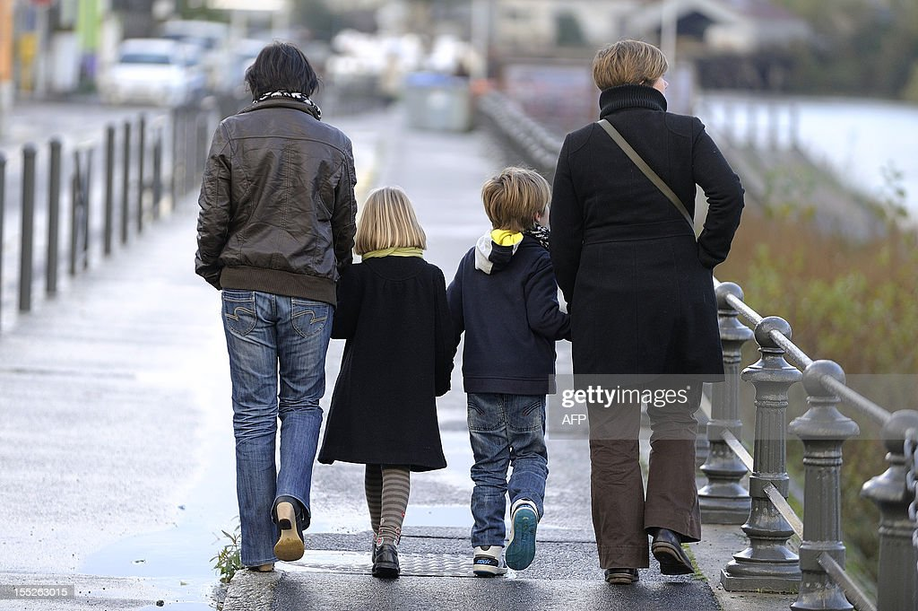 Karine Hallier (L) and her girlfriend Elodie Lucas (L) pose walking with their children on Novembre 1, 2012 at their home in Nantes, western France. The couple had two children by artificial insemination and militate for the rights to same-sex parenting.