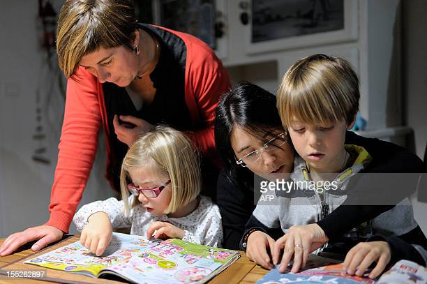 Karine Hallier and her girlfriend Elodie Lucas pose with their children on Novembre 1 2012 at their home in Nantes western France The couple had two...