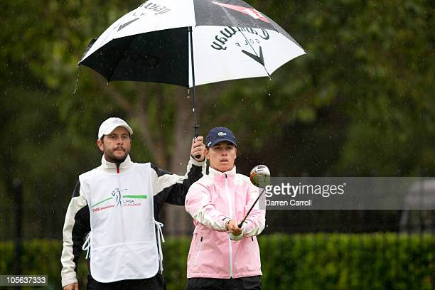 Karine Icher of France lines up a tee shot under an umbrella held by caddie Fred Bonnargent during the final round of the CVS/Pharmacy LPGA Challenge...