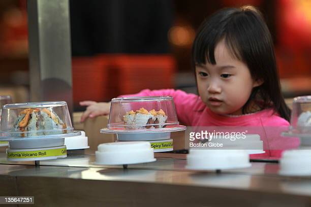 Karis Choi eating at Wasabi at the Natick Mall with her parents, not pictured, eyes the sushi and sashimi selections as they pass by on a conveyor...