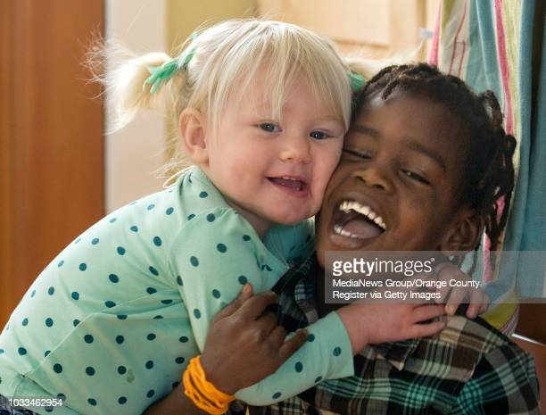 Karis Howerton months gives her brother Kembe an impromptu hug while playing together in the familiy's Costa Mesa home Kembe was adopted from Haiti...