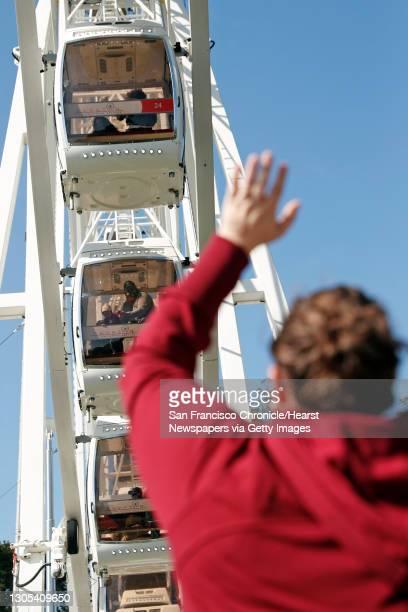 Karissa Valdez waves at her husband Gus O'Brien and their daughter, Barbara O'Brien, 21 months, as SkyStar Wheel reopens in Golden Gate Park in San...