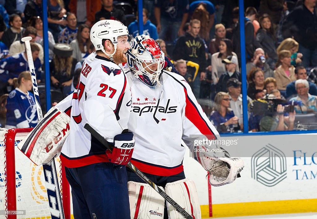 Karl Alzner #27 and Braden Holtby #70 of the Washington Capitals celebrate after defeating the Tampa Bay Lighting 4-3 during the third period of the game at the Tampa Bay Times Forum on February 14, 2013 in Tampa, Florida.