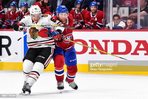 Karl Alzner of the Montreal Canadiens challenges Tanner Kero of the Chicago Blackhawks during the NHL game at the Bell Centre on October 10 2017 in...