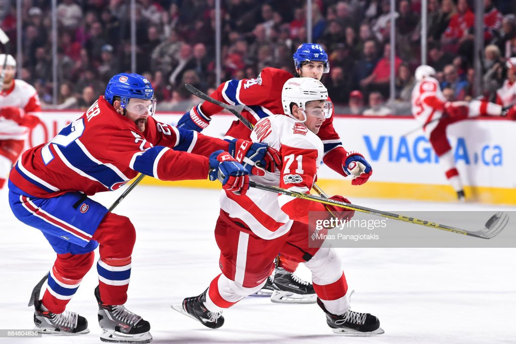 Karl Alzner #22 of the Montreal Canadiens knocks the puck with his stick near Dylan Larkin #71 of the Detroit Red Wings during the NHL game at the Bell Centre on December 2, 2017 in Montreal, Quebec, Canada. The Montreal Canadiens defeated the Detroit Red Wings 10-1.