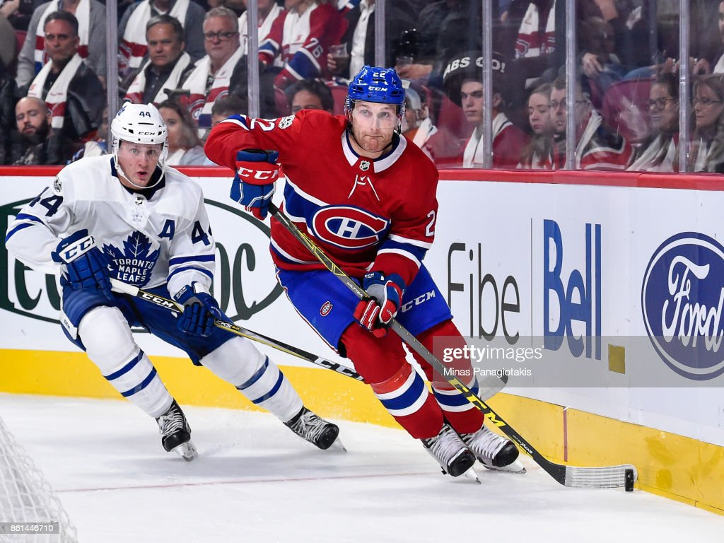 Karl Alzner #22 of the Montreal Canadiens skates the puck against Morgan Rielly #44 of the Toronto Maple Leafs during the NHL game at the Bell Centre on October 14, 2017 in Montreal, Quebec, Canada. The Toronto Maple Leafs defeated the Montreal Canadiens 4-3 in overtime.