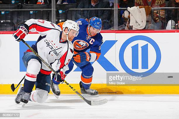 Karl Alzner of the Washington Capitals and John Tavares of the New York Islanders battle for the puck during the game at the Barclays Center on...