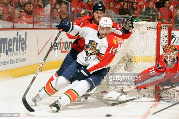 Karl Alzner of the Washington Capitals and Tomas Fleischmann of the Florida Panthers fight for the puck during a NHL hockey game on April 5 2012 at...