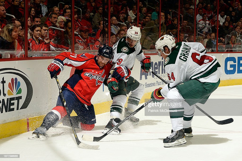 Karl Alzner #27 of the Washington Capitals battles for the puck against Mikael Granlund #64 and Jason Pominville #29 of the Minnesota Wild in overtime during an NHL game at Verizon Center on November 7, 2013 in Washington, DC.