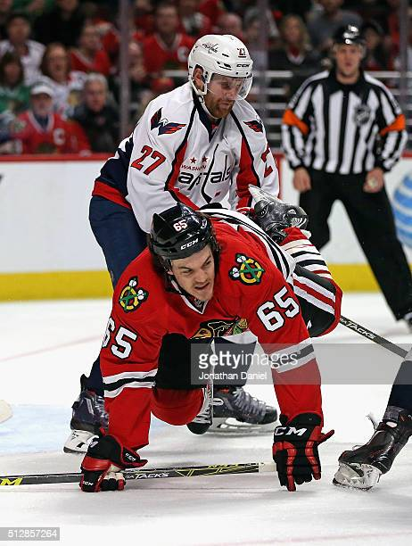 Karl Alzner of the Washington Capitals dumps Andrew Shaw of the Chicago Blackhawks to the ice at the United Center on February 28 2016 in Chicago...