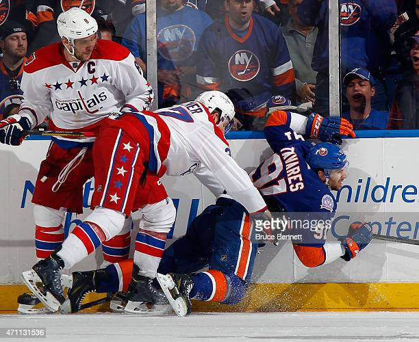 Karl Alzner of the Washington Capitals hits John Tavares of the New York Islanders into the boards during the third period in Game Six of the Eastern...