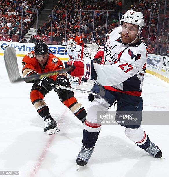 Karl Alzner of the Washington Capitals passes the puck while under pressure from Andrew Cogliano of the Anaheim Ducks on March 7 2016 at Honda Center...