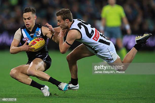Karl Amon of the Power is tackled by Tim Broomhead of the Magpies during the 2015 AFL round 15 match between Port Adelaide Power and the Collingwood...