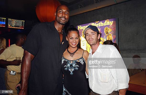 Karl and Kay Malone and Luke Perry celebrating both Los Angeles Lakers players' birthdays at the Lucky Strike on July 24 2003 in Los Angeles...