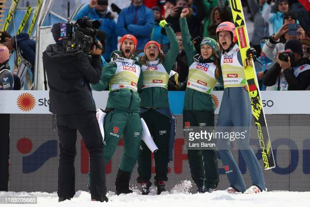 Karl Geiger of Germany Katharina Althaus of Germany Markus Eisenbichler of Germany and Juliane Seyfarth of Germany celebrates following their victory...