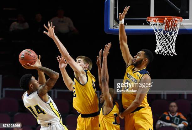 Karl Harris of the Northern Arizona Lumberjacks shoots against Tommy Rutherford Brandon Smith and Jonathan Galloway of the UC Irvine Anteaters during...