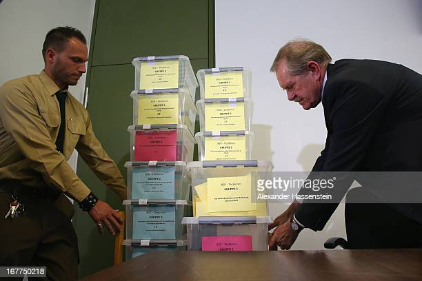 Karl Huber President of the Oberlandgericht Muenchen court carries with a police officer the lottery boxes after a press conference following the...