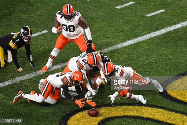 Karl Joseph, B.J. Goodson and Adrian Clayborn of the Cleveland Browns dive for a loose ball during the first half of the AFC Wild Card Playoff game...