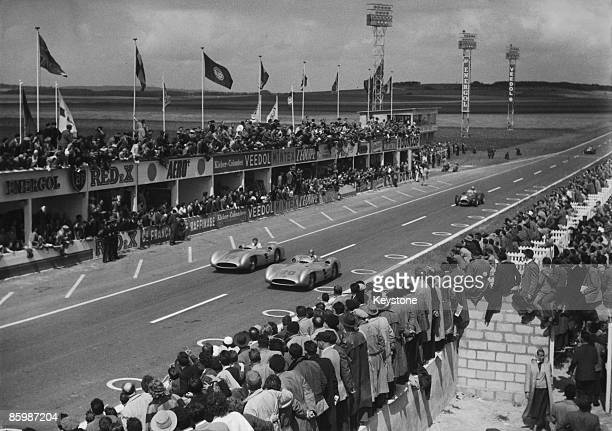 Karl Kling of Germany and JuanManuel Fangio of Argentina both driving Mercedes W196 STR cars lead the race at the French Grand Prix at Reims France...