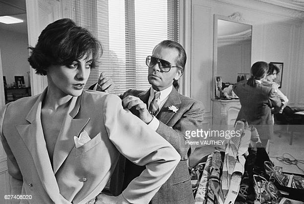 Karl Lagerfeld fits one of his designs on top model Ines de la Fressange at Chloe's Paris studio