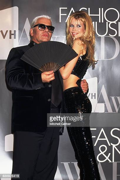 Karl Lagerfeld holds a black fan in one hand and a sequin clad Claudia Schiffer in the other on stage at the VH1 Fashion and Music Awards
