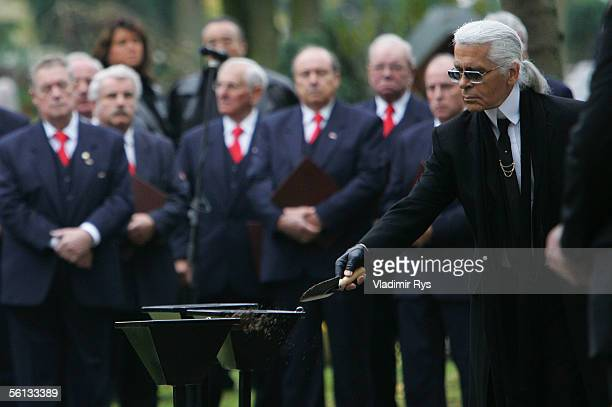 Karl Lagerfeld throws soil into the grave of Aenne Burda after the funeral service on November 10 2005 in Offenburg Germany Aenne Burda was the...