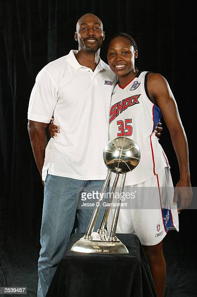 Karl Malone and daughter Cheryl Ford of the Detroit Shock celebrate with the 2003 WNBA Championship trophy after the Shock defeated the Los Angeles...