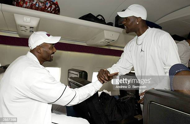 Karl Malone and Gary Payton of the Los Angeles Lakers greet each other on the plane befor leaving for training camp October 2 2003 in Honolulu Hawaii...