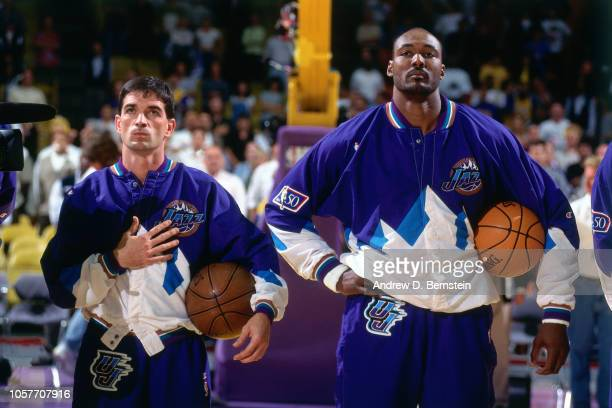 Karl Malone and John Stockton of the Utah Jazz stand for the National Anthem during Game Three of the Western Conference Semifinals as part of the...