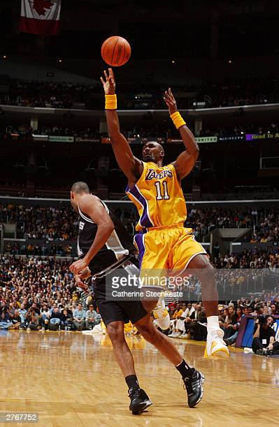 Karl Malone of the Los Angeles Lakers bumps into Tim Duncan of the San Antonio Spurs during the first half at Staples Center November 28 2003 in Los...