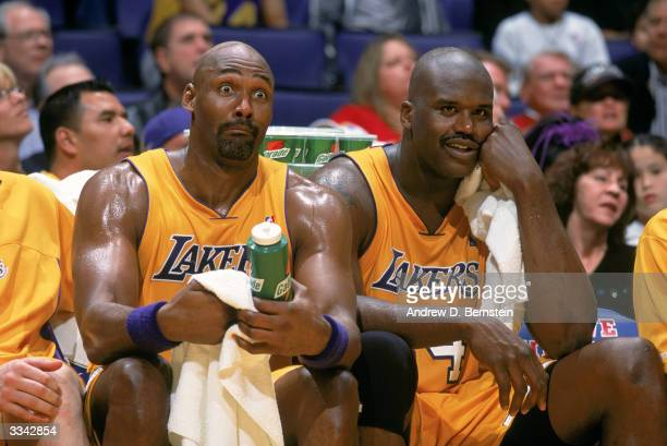 Karl Malone of the Los Angeles Lakers talks with Shaquille O'Neal on the bench during the game against the Houston Rockets at the Staples Center on...