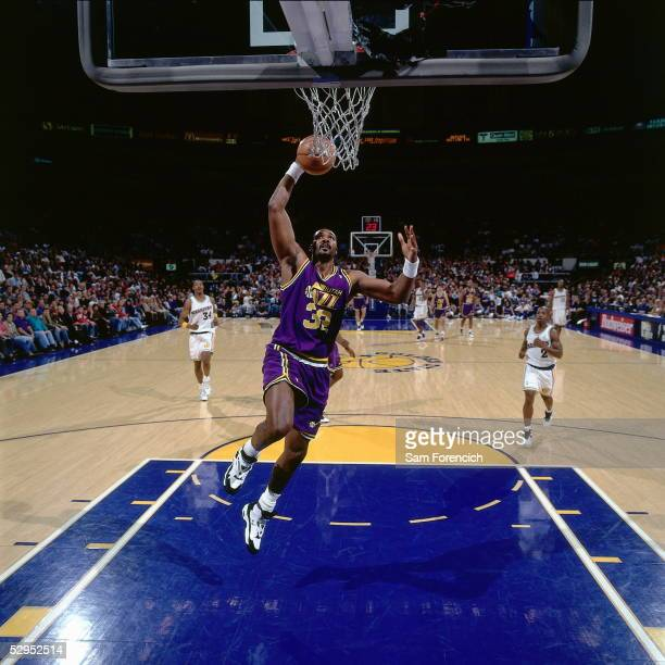 Karl Malone of the Utah Jazz drives to the basket for a layup against the Golden State Warriors at the Arena at Oakland circa 1995 in Oakland,...