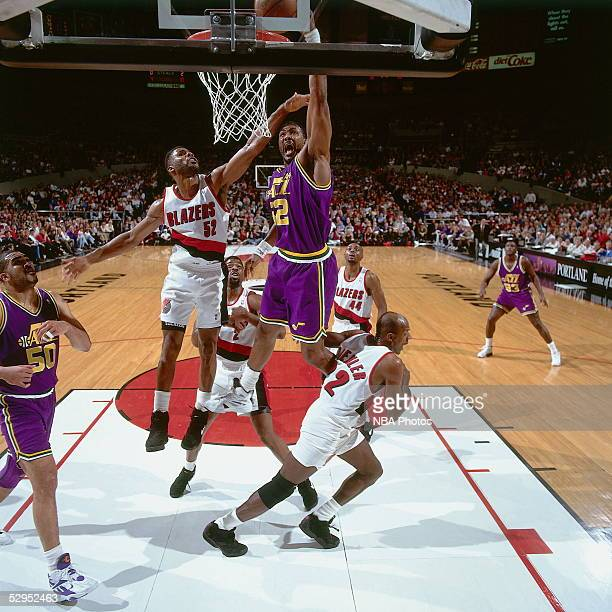 Karl Malone of the Utah Jazz drives to the basket for a slam dunk against Buck Williams of the Portland Trail Blazers circa 1994 in Portland Oregon...