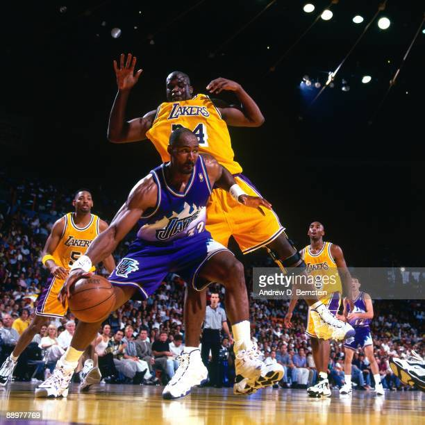 Karl Malone of the Utah Jazz makes a move to the basket against Shaquille O'Neal of the Los Angeles Lakers in Game Four of the Western Conference...