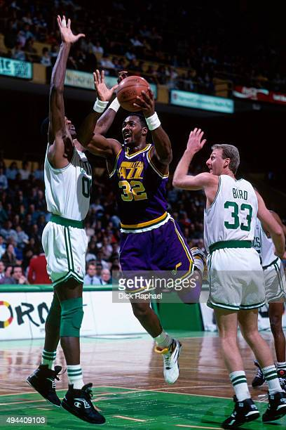 Karl Malone of the Utah Jazz shoots against Robert Parish and Larry Bird of the Boston Celtics during a game played in 1992 at the Boston Garden in...