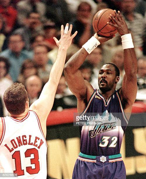 Karl Malone of the Utah Jazz shoots over Luc Longley of the Chicago Bulls 12 June during game five of the NBA Finals at the United Center in Chicago...
