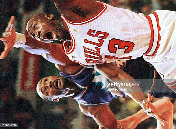 Karl Malone of the Utah Jazz tries to block a shot by Michael Jordan of the Chicago Bulls 04 June during the second half of game two of the NBA...