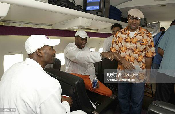 Karl Maolne Horace Grant Rick Fox and Derek Fisher of the Los Angeles Lakers on the plane before leaving for training camp October 2 2003 in Honolulu...