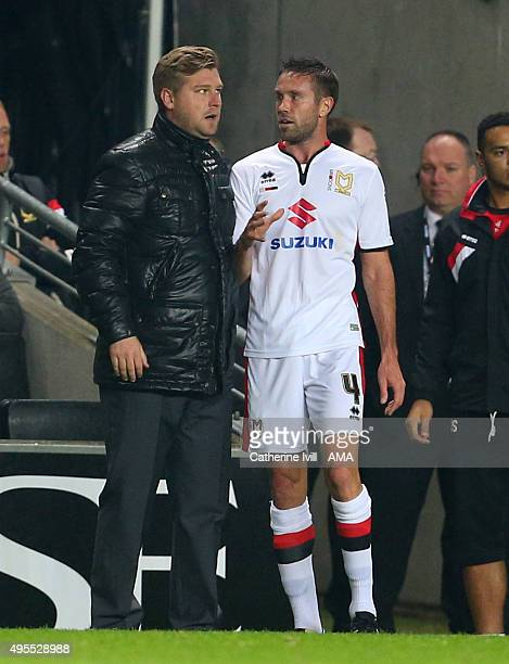 Karl Robinson manager of MK Dons talks to Matthew Upson of MK Dons as he goes off injured during the Sky Bet Championship match between MK Dons and...