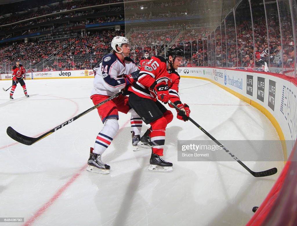 Karl Stollery #46 of the New Jersey Devils is checked by Josh Anderson #34 of the Columbus Blue Jackets at the Prudential Center on March 5, 2017 in Newark, New Jersey. The Blue Jackets shutout the Devils 3-0.