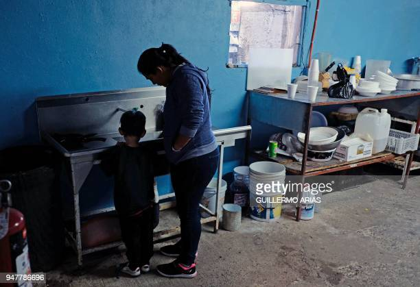 Karla and her son from El Salvador wash the dishes during the Migrant Via Crucis caravan composed mainly by Central American migrants at Juventud...