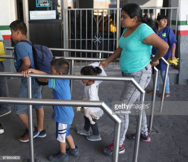 A migrant mother who is waiting to seek asylum for herself and her two daughters in the US gathers with another migrant in a shelter for migrant...