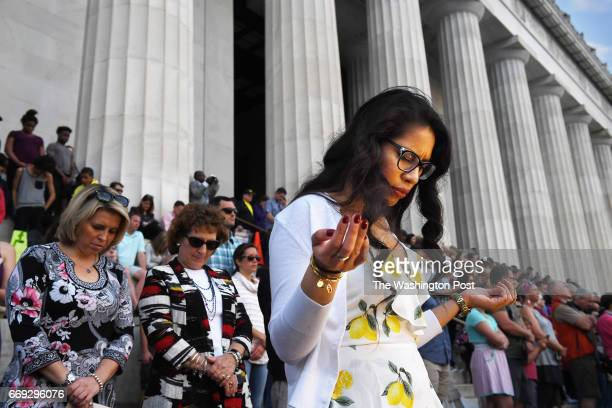 Karla Mercado prays with others at the Lincoln Memorial for the annual Easter sunrise service on Sunday April 16 2017 in Washington DC