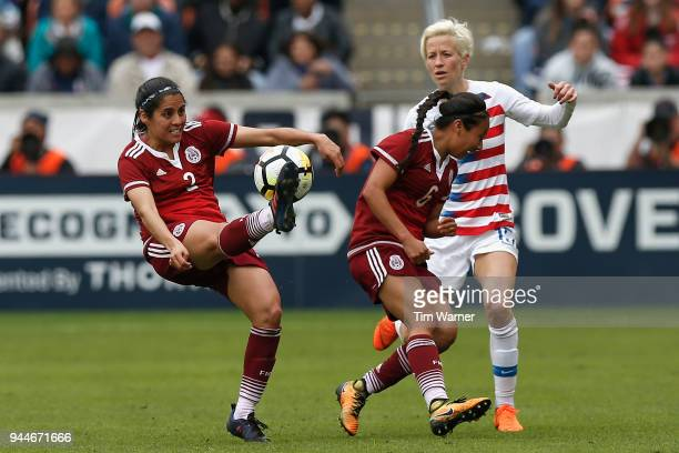 Karla Nieto of Mexico reacts as Kenti Robles clears the ball in front of Megan Rapinoe of United States in the second half at BBVA Compass Stadium on...